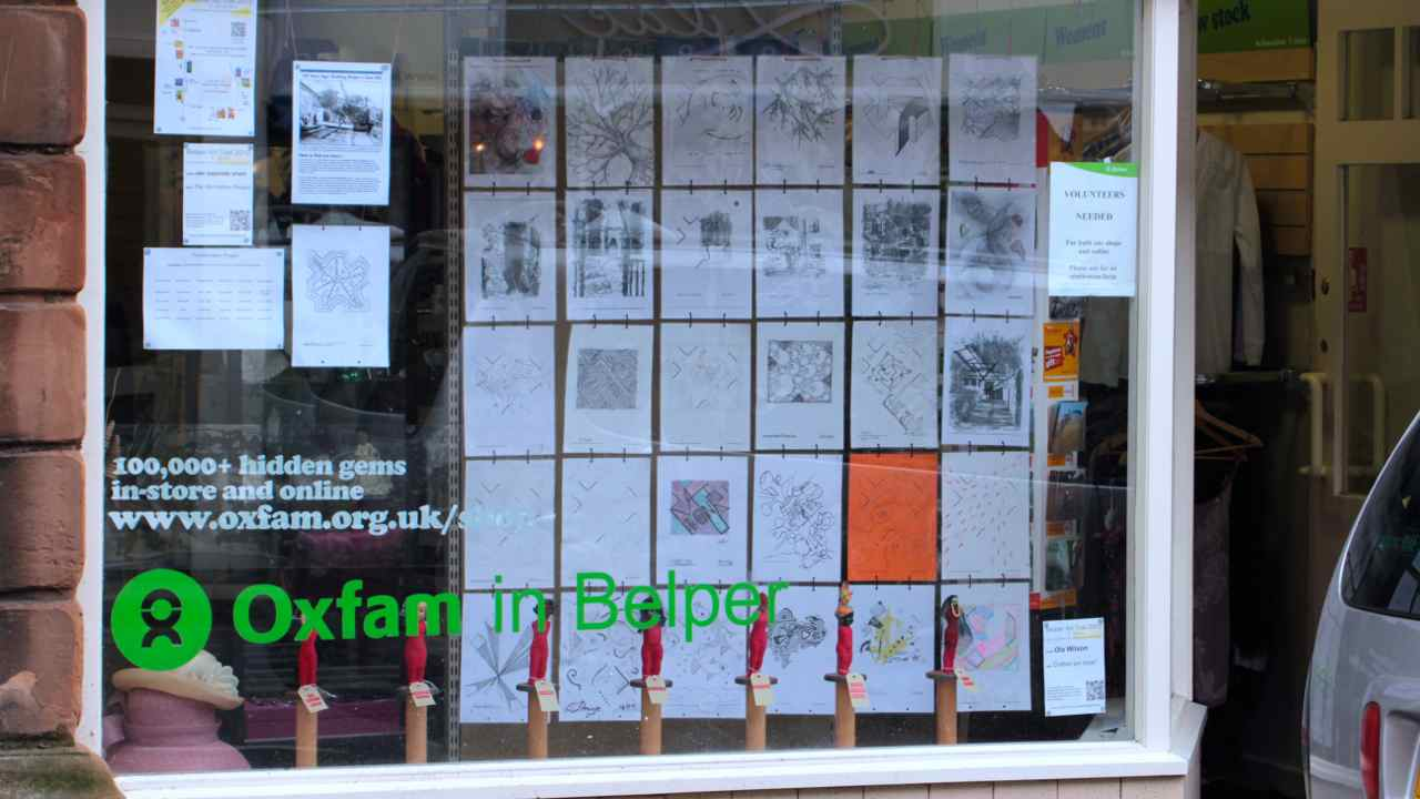 thirty drawings hanging in a shop window