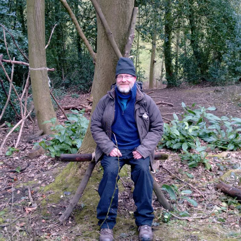 a woodland seat made from three logs leant against a tree